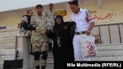 عناصر من قوات الأمن المصرية تساعد سيدة بعد الإدلاء بصوتها في الإنتخابات