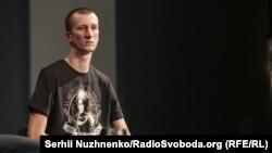 Олександр Кольченко на пресконференції в Києві, 10 вересня 2019 року. На футболці портрет Нестора Махна