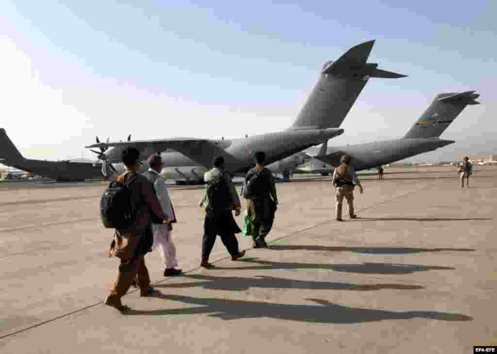 Aliniați, oamenii se pregătesc să urce la bordul unei aeronave militare, în timpul operațiunilor de evacuare care se desfășoară pe aeroportul din Kabul, 23 august.