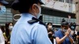Hongkongi rendőrök figyelnek 2021. április 4-én egy demokráciapárti aktivistát, aki azokra emlékezik, akiket 1989-ben a pekingi Tienanmen téren gyilkolt meg a kínai hadsereg