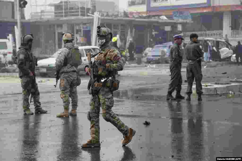 Members of the Afghan security forces inspect at the site of the attack.