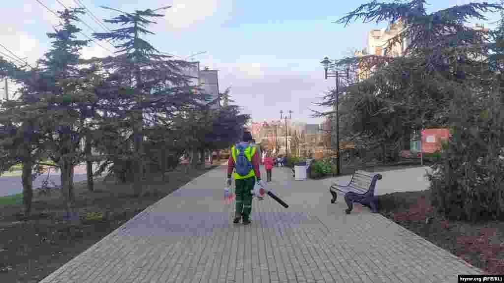 Робочий із повітродувом здуває бруд з тротуарної плитки