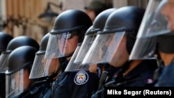 Полиция в защитном снаряжении выстроилась в линию во время демонстрации в центре Торонто 25 июня 2010 года перед саммитом G20.