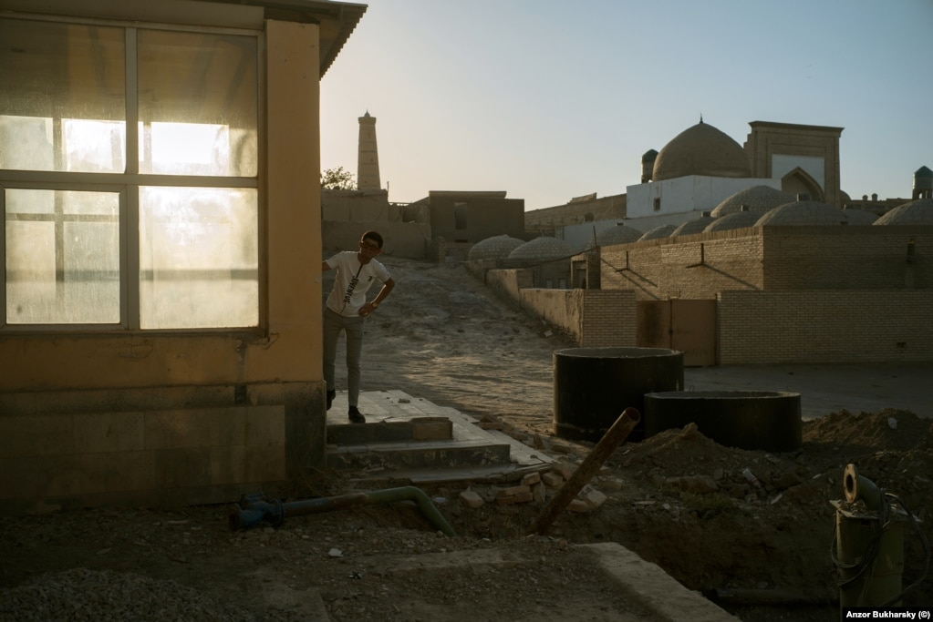 A man peers from the entrance to a building in Khiva next to where major earthworks are under way.