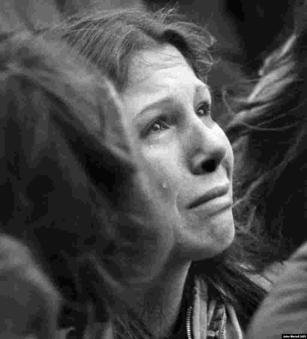 На цій фотографії з архіву від 14 грудня 1980 року жінка плаче під час десятихвилинного мовчання на честь Джона Леннона, яке відбулося перед церквою Трійці в Бостоні (США). За оцінками приблизно 2000 людей зібралися вшанувати пам'ять колишнього «Бітла», убитого в Нью-Йорку