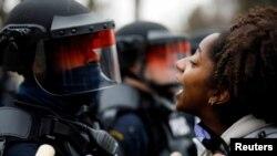 Протестующая жительница города Бруклин-Сентер и полицейский — вскоре после инцидента с гибелью молодого афроамериканца, 11 апреля 2021 года.