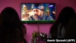 A family watches the Turkish drama series Dirilis: Ertugrul on Pakistani TV during the holy month of Ramadan in Islamabad.