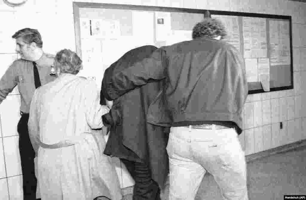 Марку Чепмену (на фото в центрі), підозрюваному у вбивстві Джона Леннона, наділи бронежилет і накинули на голову пальто, щоб ніхто не бачив його обличчя, і таким чином доправили його з поліцейського відділку в кримінальний суд Нью-Йорка