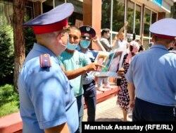 Наразылар полиция қызметкерлеріне Шыңжаңдағы қудалаулар туралы айтып жатыр. Алматы, 24 маусым 2021 жыл.