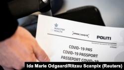 Një person në Daminarkë duke mbajtur në duar në pasaportë për koronavirusin të lëshuar nga autoritetet daneze. Fotografi nga arkivi.