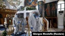 Архивска фотографија- луѓе во скафандери носат ковчег на починат од Ковид19, Грција