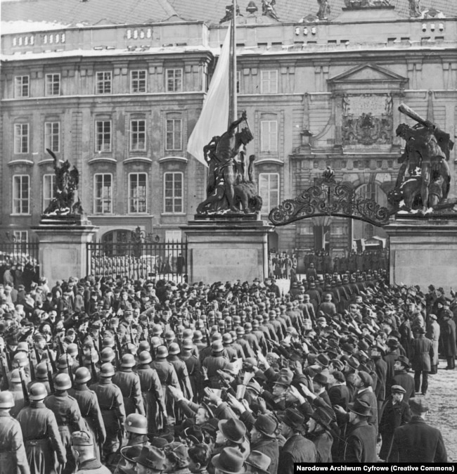 Nazi troops march into Prague Castle as crowds salute them in March 1939.