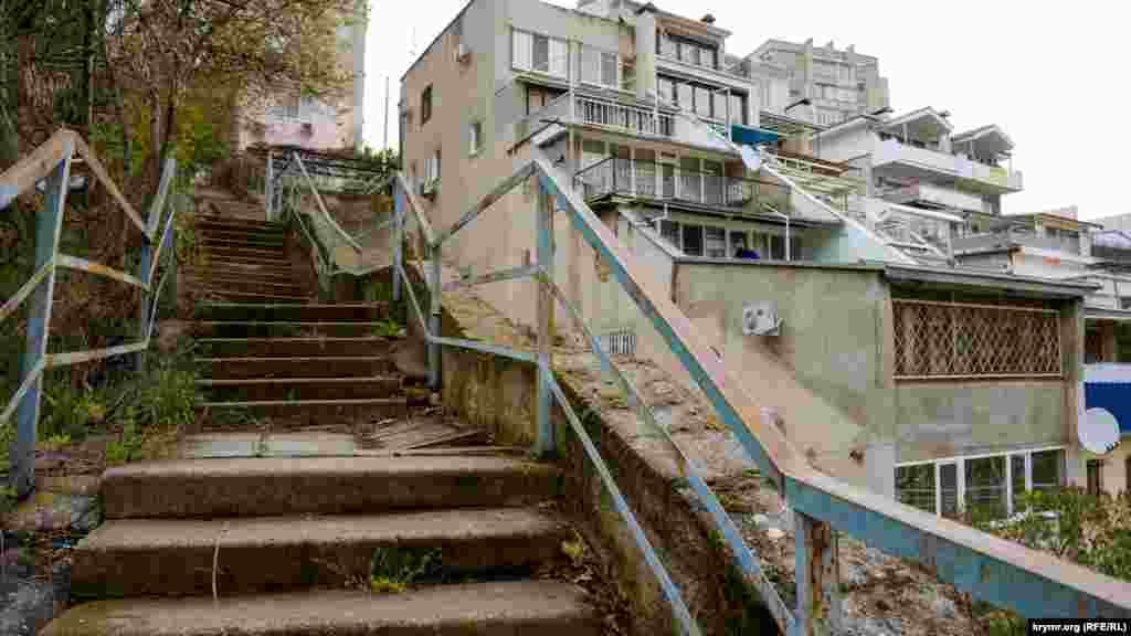Старая лестница у многоквартирного дома с террасами, обращенными к морю