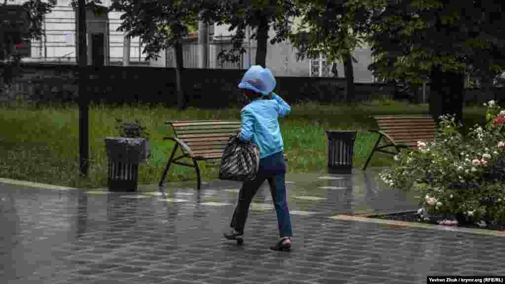 Вместо зонта женщина использует полиэтиленовый пакет
