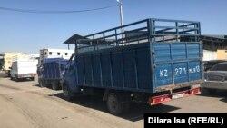 Колонна грузовых машин у въезда на территорию рынка