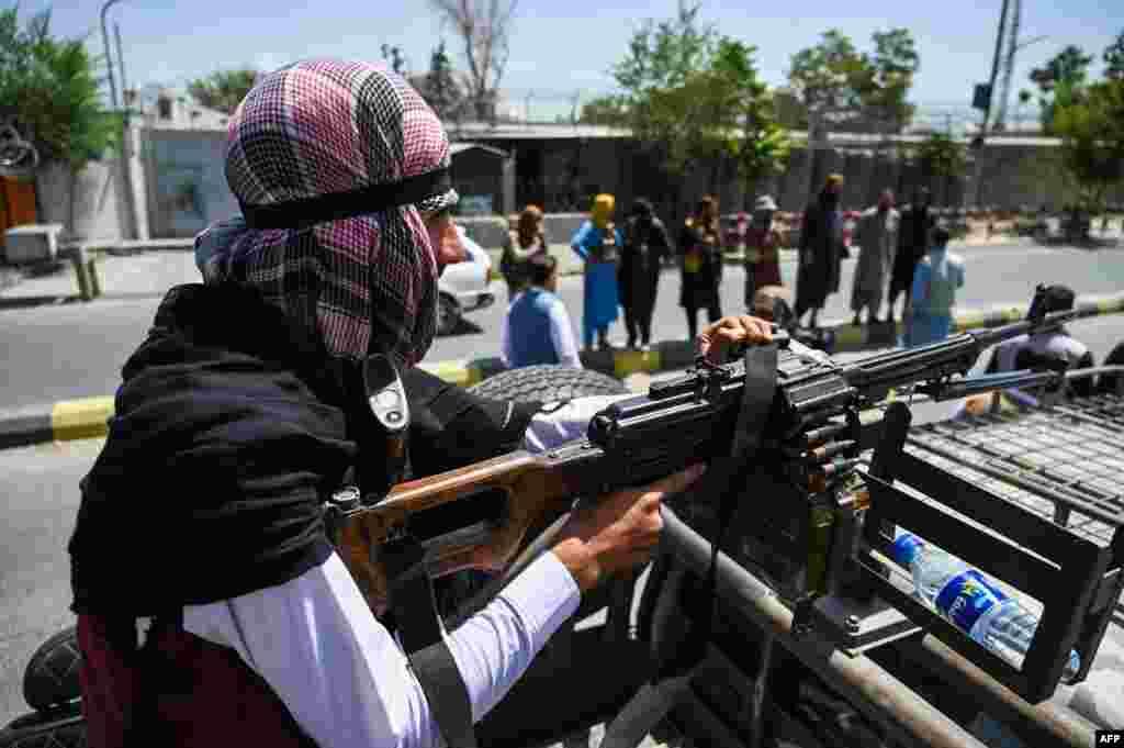 Боец на талибаните е в готовност с картечница в каросерията на пикап. Други талибани патрулират по улица в Кабул.