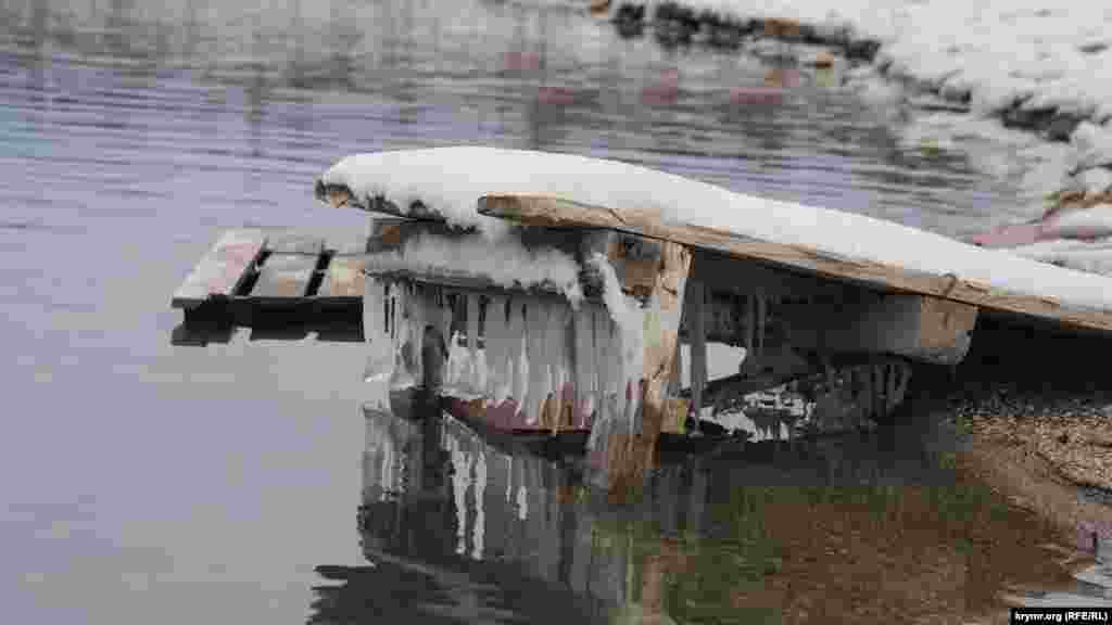 Бурульки під дерев'яним настилом на березі водосховища
