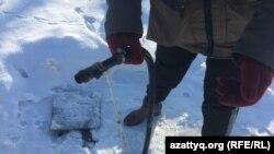 Галина Федюшко показывает шланг, откуда местные жители берут питьевую воду. Село Радовка, Акмолинская область, 30 ноября 2020 года.