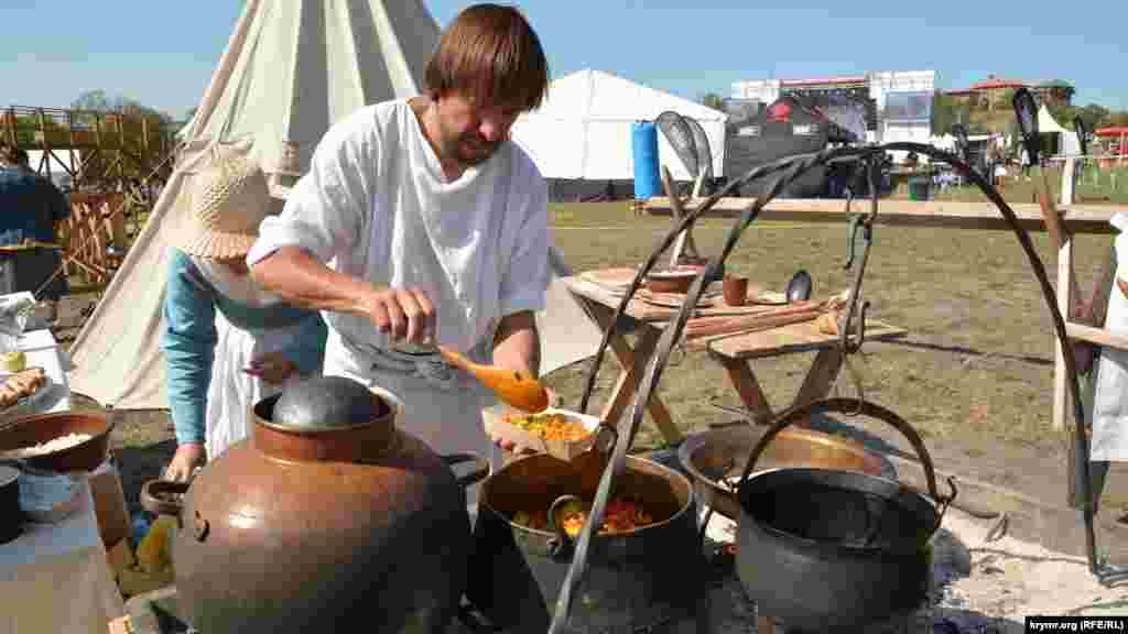 Реконструктор подает средневековое генуэзское блюдо в картонной коробочке на празднике виноделия в Балаклаве