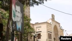 Nedavni izbori koje je organizovao sirijski režim ne mogu voditi bilo kakvim merama međunarodne normalizacije, rekao je portparol EU Peter Stano. Na slici: plakat Bašara al-Asada kod zgrade parlamenta u Damasku uoči predsedničkih izbora u Siriji, 18. april 2021.