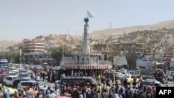 Флаг талибов на постаменте с людьми, собравшимися вокруг главной городской площади в Пули-Хумри 11 августа 2021 года после того, как талибы захватили Пули-Хумри, столицу провинции Баглан, примерно в 200 км к северу от Кабула