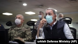Turkish Defense Minister Hulusi Akar, right, and Chief of Staff Gen. Yasar Guler wearing face masks to protect against the coronavirus, monitor the operation at a military headquarters in Ankara, June 15, 2020