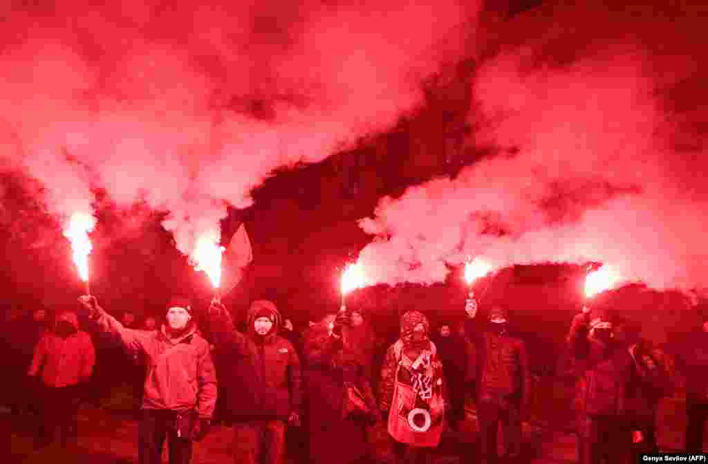 ...while these people burn flares at the rally.