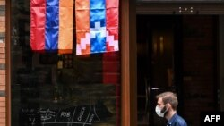 ARMENIA -- A man walks past a shop decorated with flags of Armenia and Nagorno-Karabakh in Yerevan, October 6, 2020