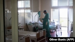 A medical worker treats a patient suffering from COVID-19 at a hospital in Belgrade on July 14.