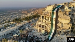 На снимке, сделанном в конце августа 2020, противники Асада проводят митинг у здания, разрушенного авиаударами. Город Эриха, провинция Идлиб, Сирия.