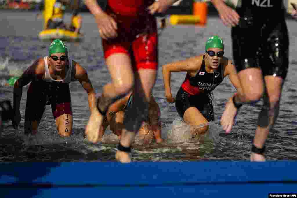Угорка Жанетт Брагмаєр (ліворуч) та Юко Такахаші з Японії виходять із води під час змішаної естафети у змаганнях з триатлону. Токіо, 31 липня 2021 року