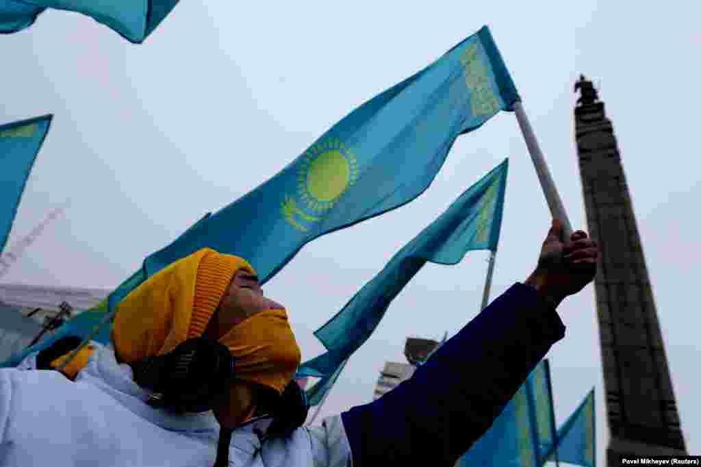 Kazakhs hold national flags near the Monument of Independence during a gathering marking Independence Day in Almaty on December 16. (Reuters/Pavel Mikheyev )