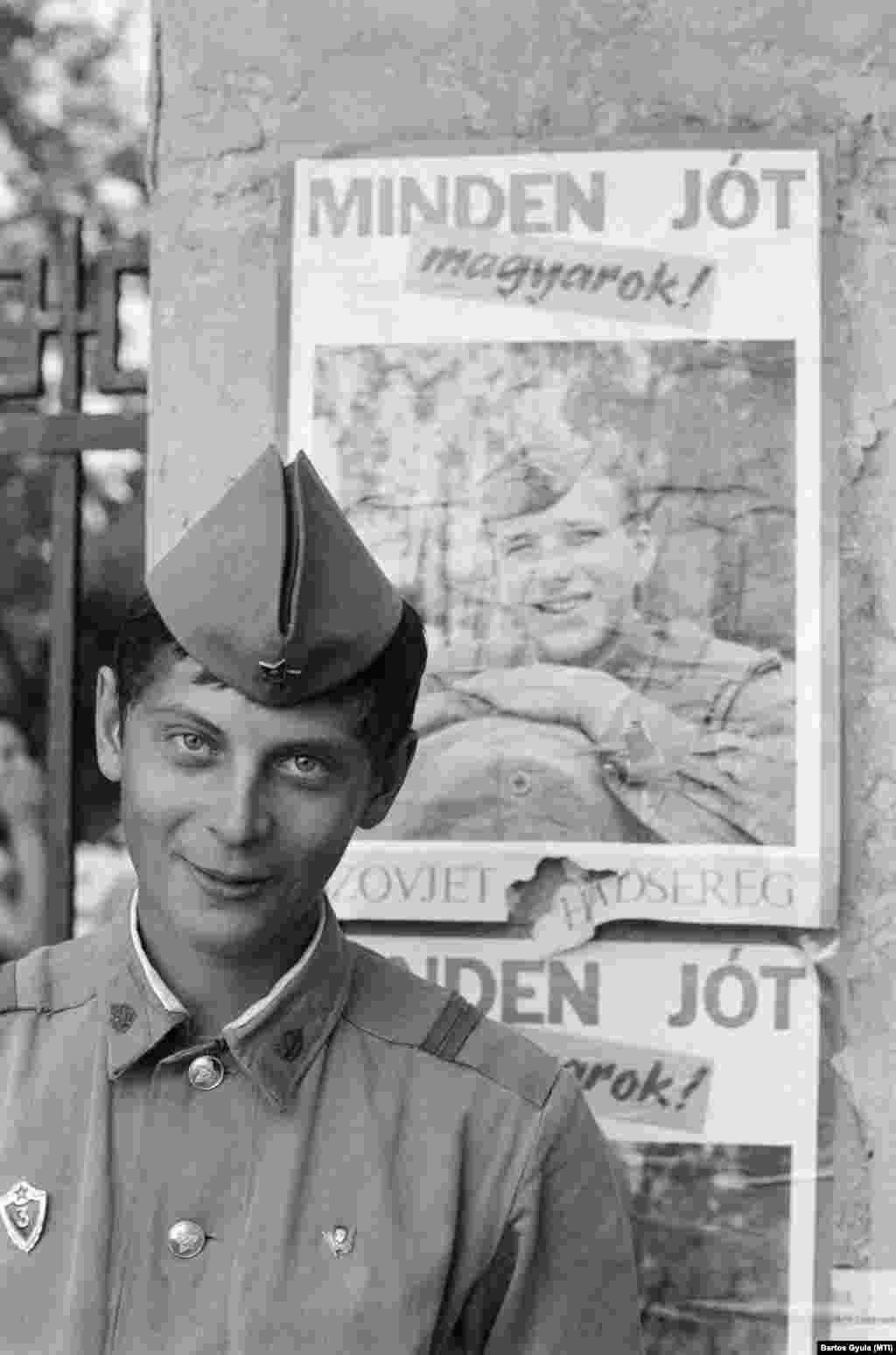 Budapest, 1990. május 18. Egy szovjet katona, mögötte a kivonuló szovjet hadsereg búcsúplakátja a pestújhelyi szovjet katonai kórház kerítésén.