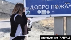 A woman is crying near a road sign welcoming people to Nagorno-Karabakh in Kalbajar as Armenians prepare to hand the district over to Azerbaijan as part of a ceasefire agreement. November 12, 2020.