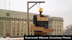 """Cardboard signs say """"Business"""" at the top, with """"Loans,"""" Taxes,"""" and """"Electricity Bills"""" below"""
