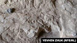 Вырезанные на полу пещеры символы