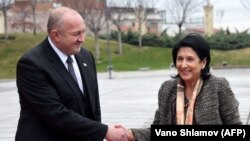 Giorgi Margvelashvili (solda) yeni seçilmiş prezident Salome Zurabishvili ilə görüşür
