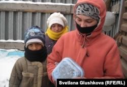16-летняя Гульмира Арзыкулова (справа) высыпает себе собранную мелочь. Рядом брат Шакрукх (слева) и сестренка Азиза. Астана, 15 ноября 2012 года.