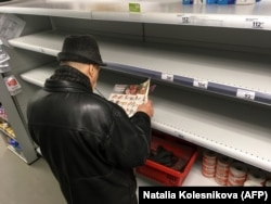 A man stands in front of empty shelves in a supermarket in Moscow on March 17.