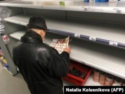 Мужчина на фоне пустых полок супермаркета в Москве.