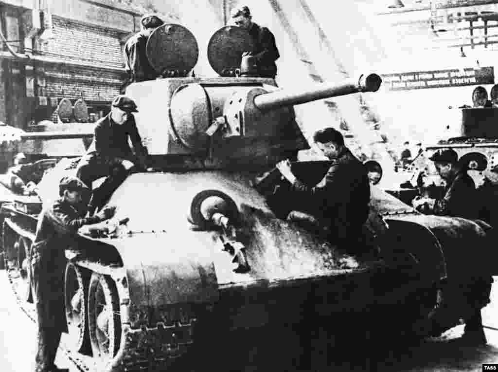 Workers assemble a T-34 tank at the Uralmash Machine-Building Plant during World War II in Sverdlovsk, U.S.S.R., 1942.