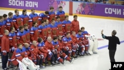 Russian ice-hockey team players pose for a family photo during a training session during the Sochi Winter Olympics February 2014.