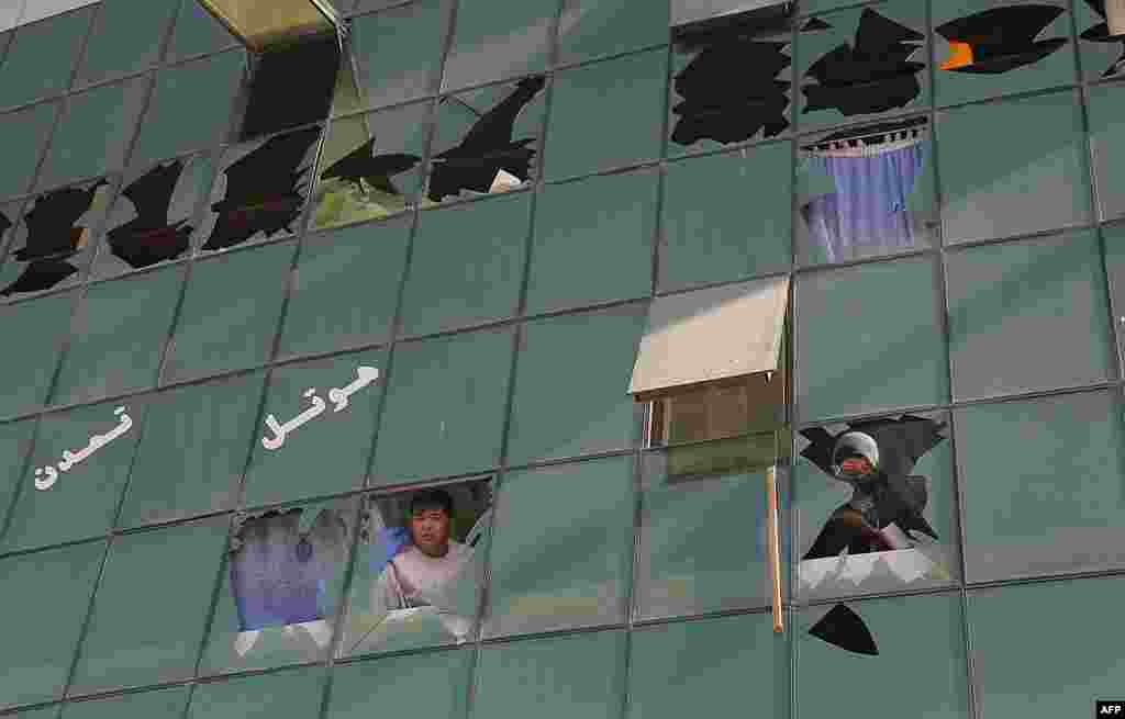 Men peer through broken windows following a suicide attack in Ghazni, Afghanistan, on September 4. A Taliban truck-bomb attack on a government compound killed 13 security personnel and left at least 60 other people wounded. (AFP/Rahmatullah Alizadah)