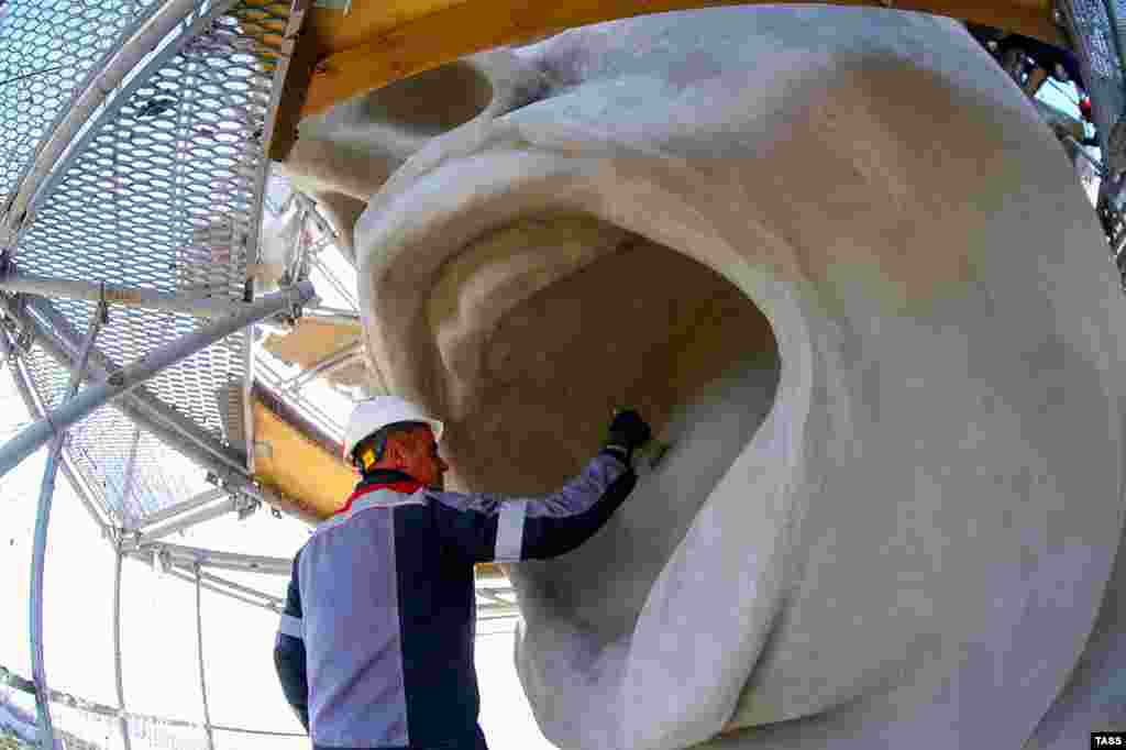 A worker brushes the statue's tongue. Weathering of the monument has been an ongoing issue, with the harsh climate of southern Russia leading to chips of concrete flaking off.