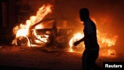 رجل ينظر الى سيارة مفخخة بعد إنفجارها في بغداد