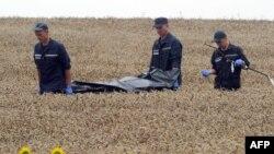 Українські рятувальники несуть тіло жертви катастрофи літака MH17, 19 липня 2014 року, Грабове, Донецька обасть, Україна