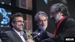 مسعود کیمیایی (راست) جایزه خود را از معاون سینمایی وزارت ارشاد میگیرد