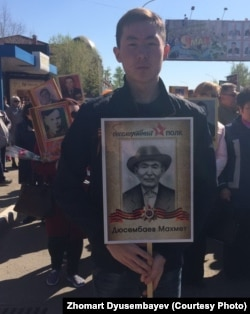 Юноша с портретом бывшего военнопленного Махмета Дюсембаева на шествии «Бессмертный полк», прошедшем 9 мая 2017 года в Кокшетау. Фотография Азаттыку предоставлена Жомартом Дюсембаевым.