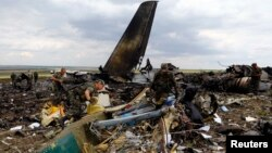 Бойовики риються в уламках збитого літака, фото 14 червня 2014 року