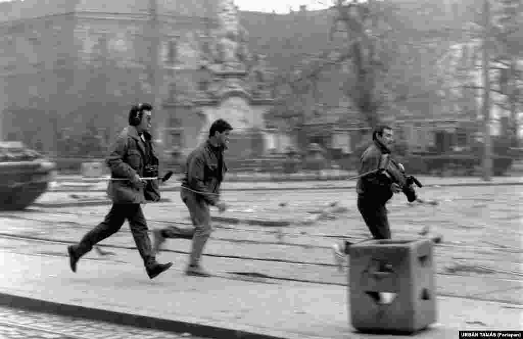 A television crew runs into position in Timisoara during the revolution. After Romanian security services shot many demonstrators dead in Timisoara, a larger demonstration in Bucharest eventually led to the overthrow of the communist regime. Ceausescu and his wife, Elena, were executed on December 25, 1989.